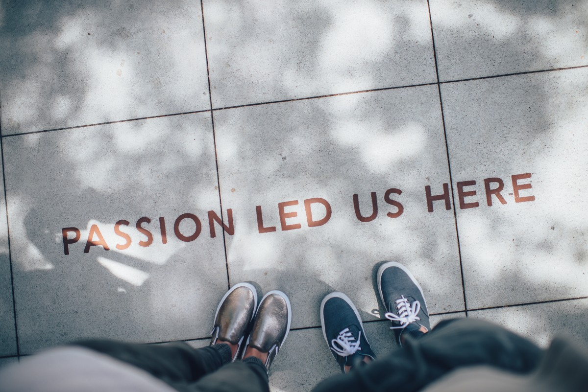 """Standing over sidewalk art that reads """"passion lead us here""""."""