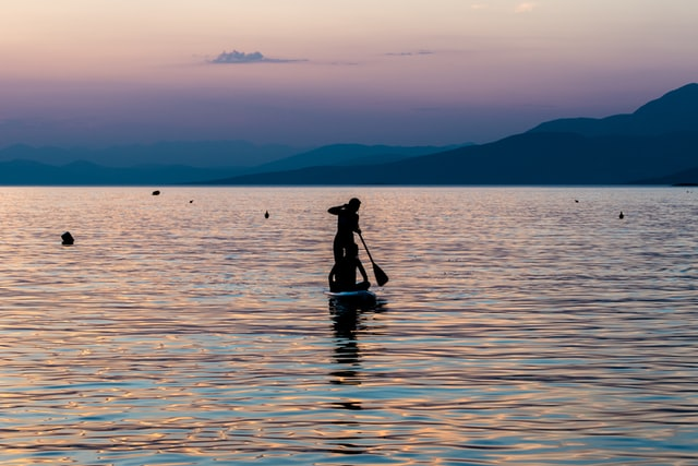 two kids paddleboarding into the sunset in greece