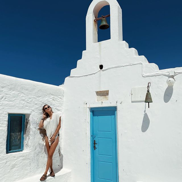 a girl in summer clothes next to a little chapel in mykonos, greece