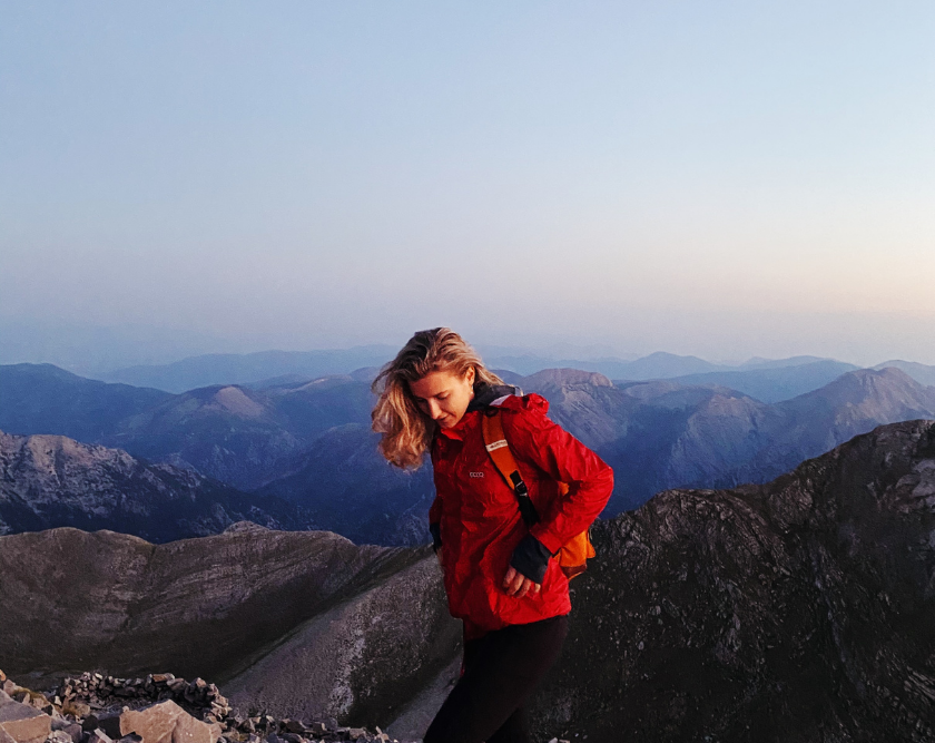 Giota at the top of a mountain in Greece, with the sunrise behind