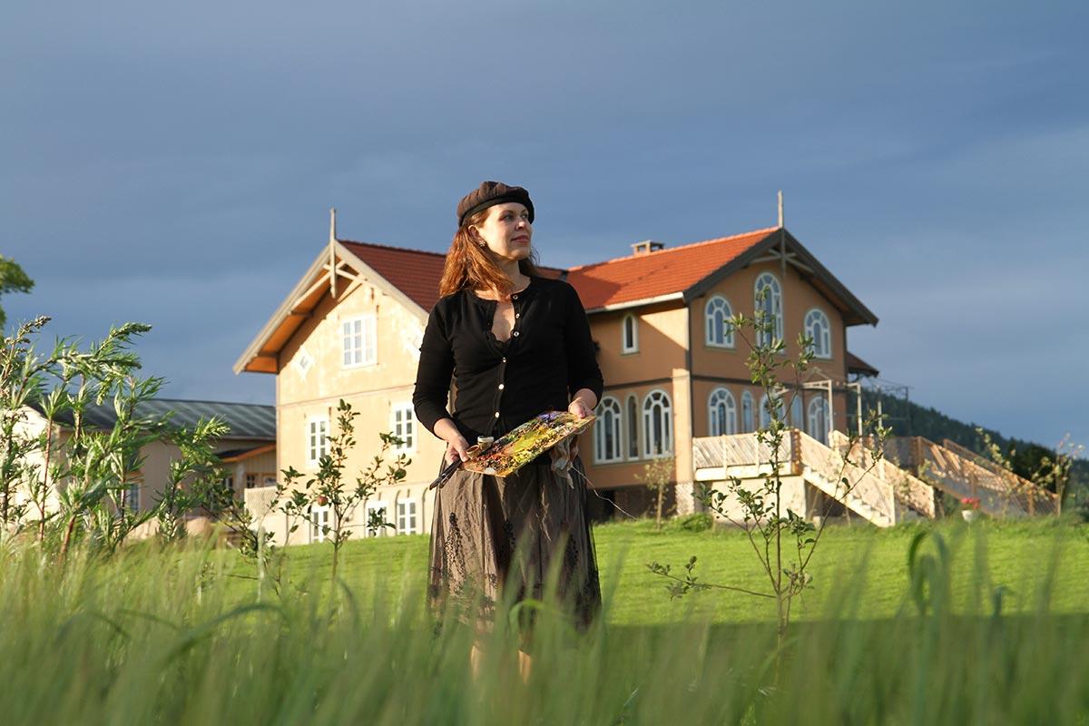 Kunstmaler Elisabeth de Lunde på gressengen foran Villa Lunde i Telemark