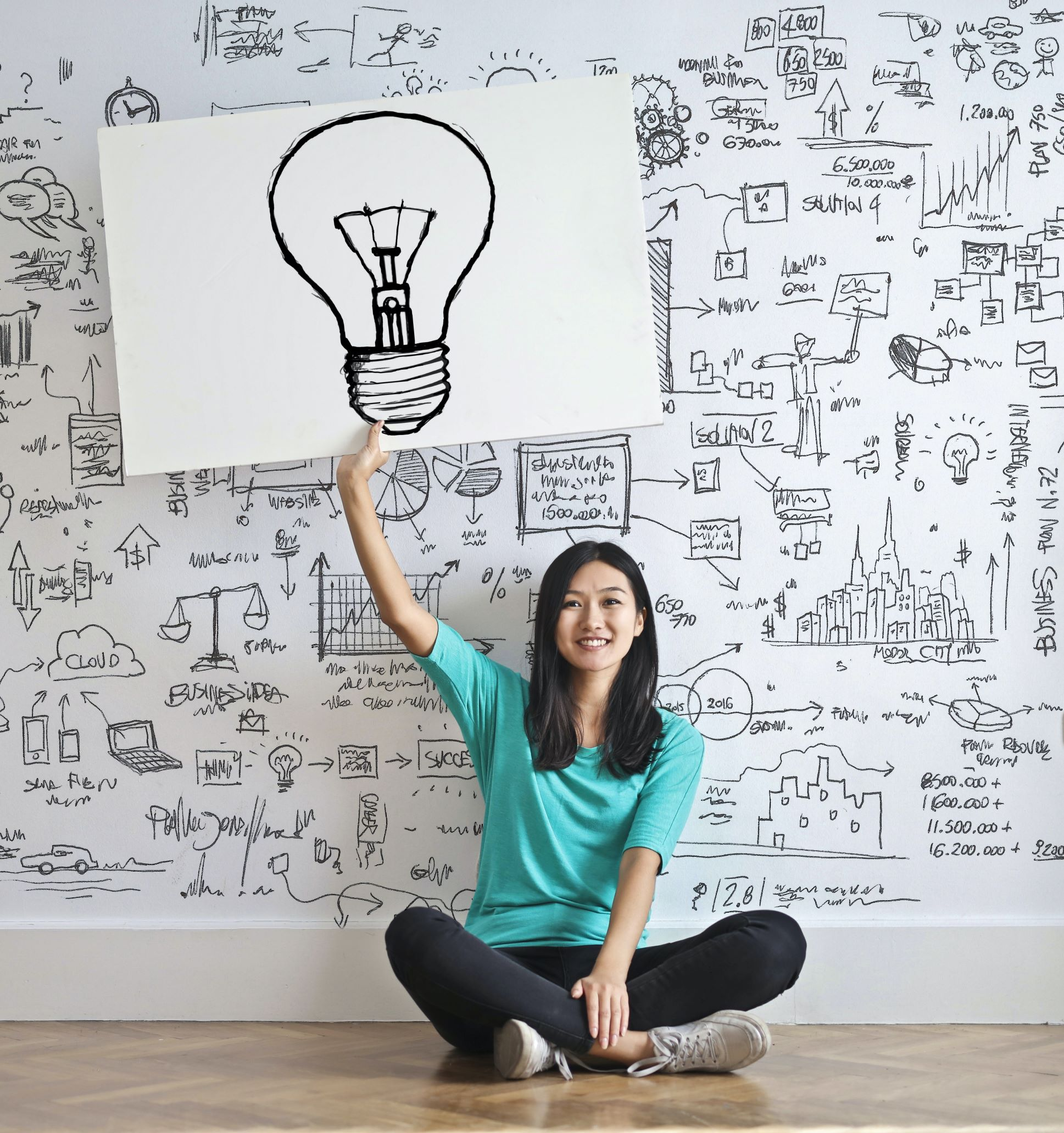 Woman holding a drawing of a lightbulb.