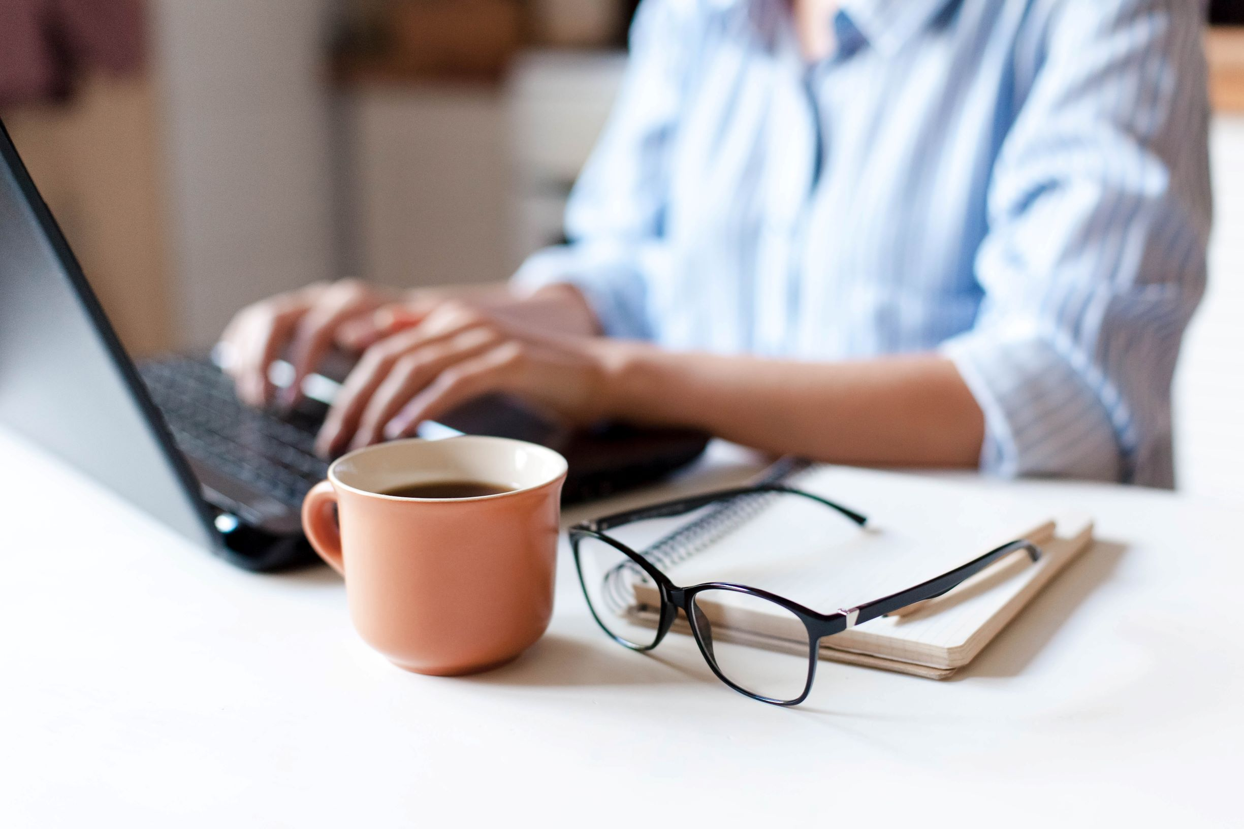 A person typing on a computer at a desk with a cup of coffee, glasses, and notepad nearby.