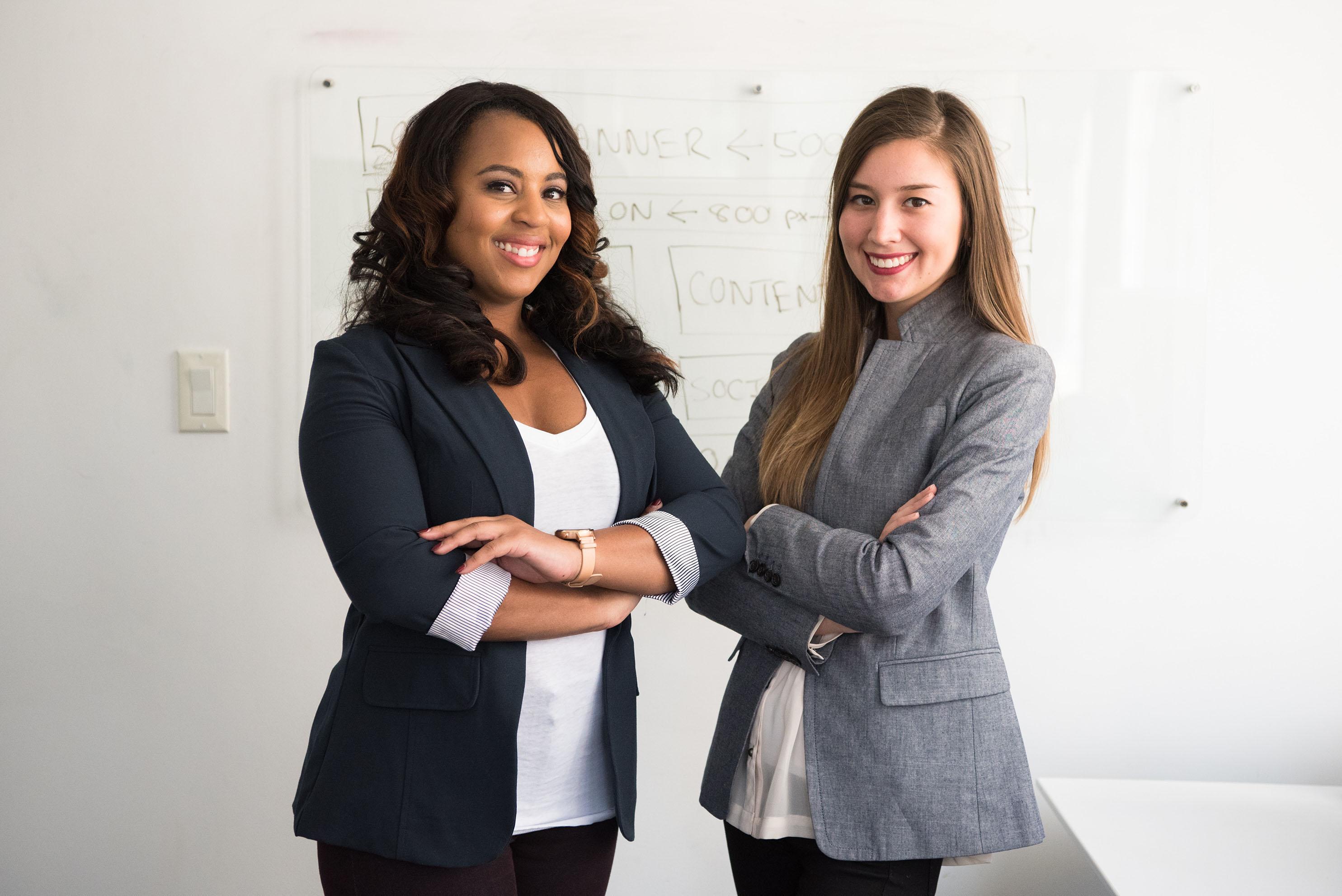 deux femmes les bras croisés devant un tableau blanc orthographiq
