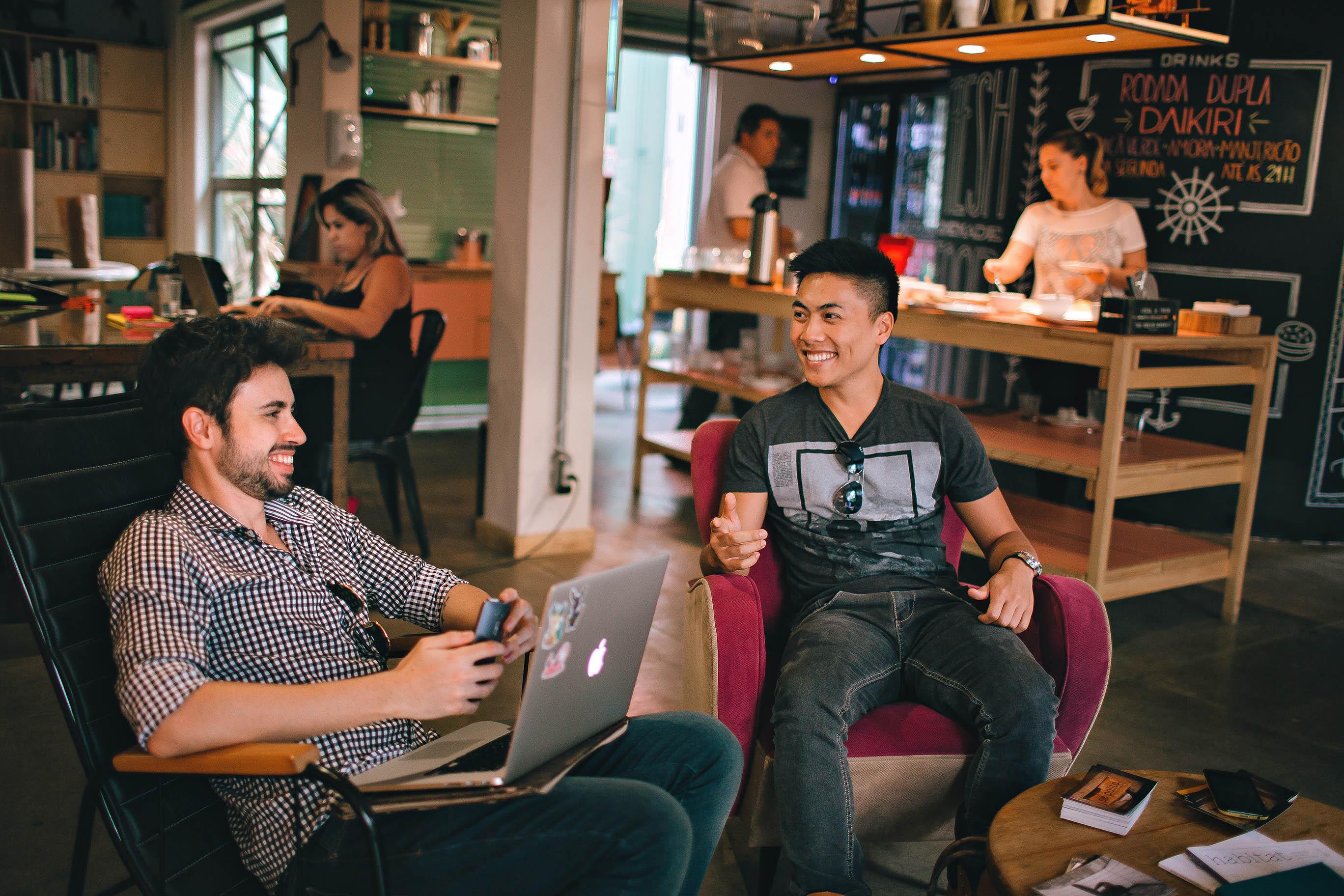 deux hommes installés dans des fauteuils, l'un avec un ordinateur orthographiq