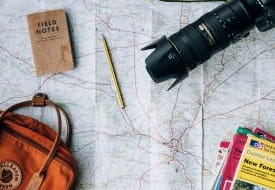 a camera and a backpack on a map