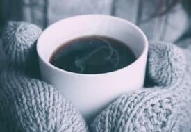 gloved hands holding a mug of coffee