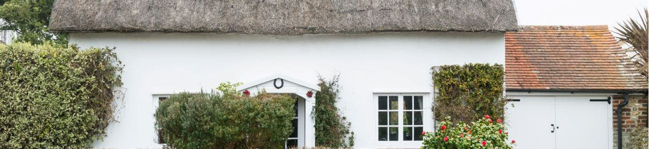 A white thatched property surrounded by roses
