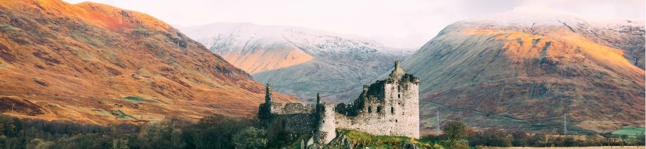 A castle on a lake surrounded by mountains in Scotland