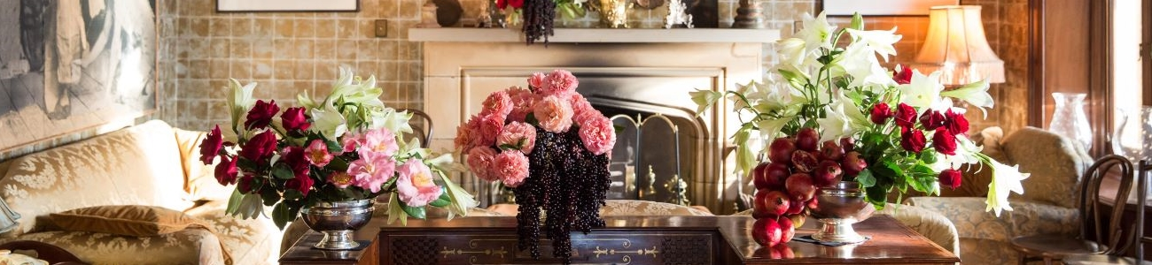 A living room fire place surrounded by vases of flowers