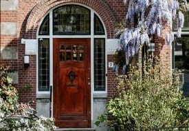 A wooden door set in a red brick house covered in plants