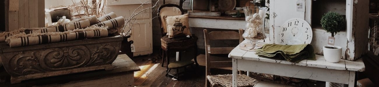 A cluttered room with aged items including clocks, chairs, tables and ceramics
