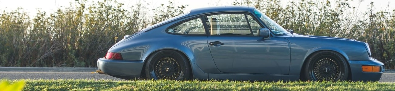 A classic car on a roadside set against long grass