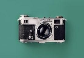 A retro, film camera on a green background