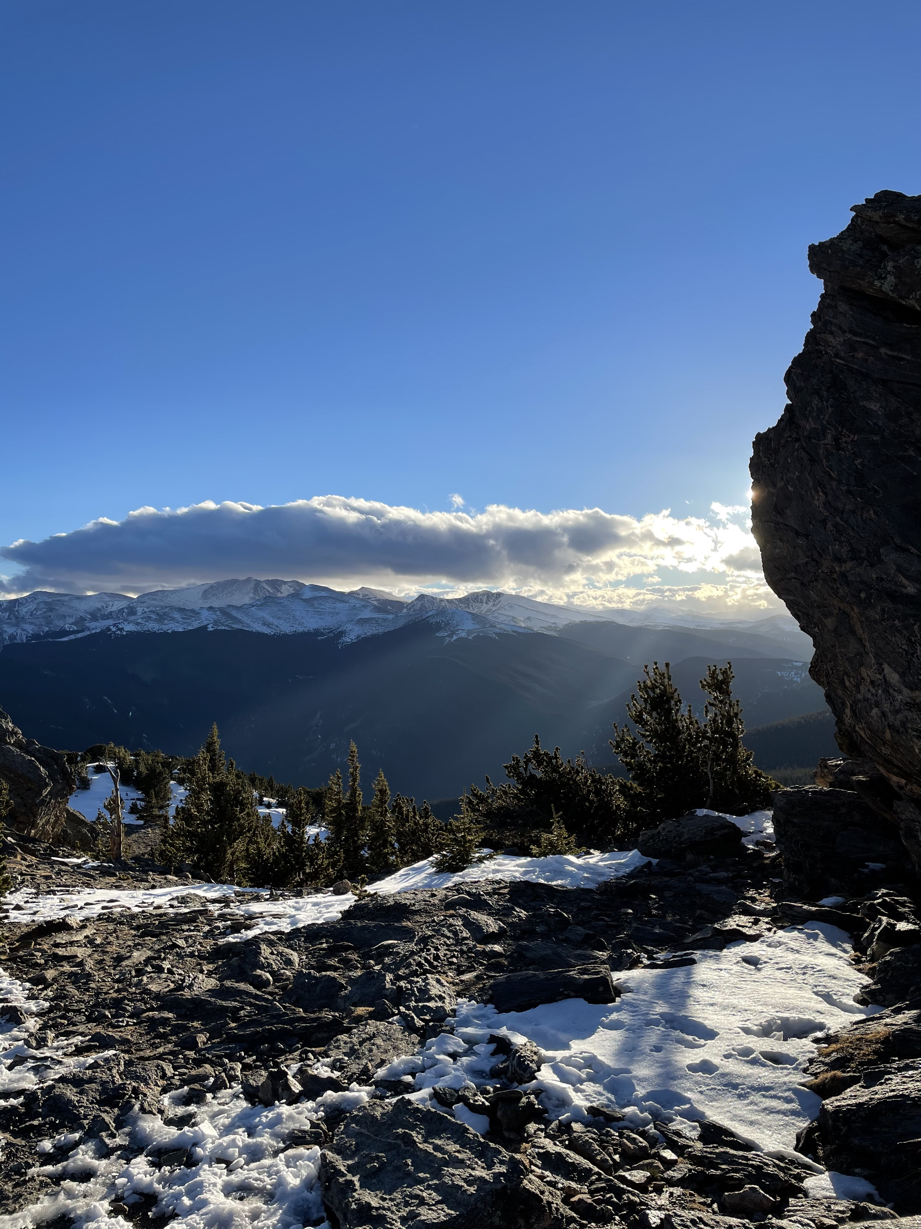 sun peaking around a rock, view of the mountains with clouds overhead and a snow covered ground