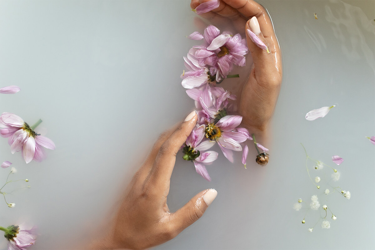 Flowers floating in silky water, gently held by a woman's hands