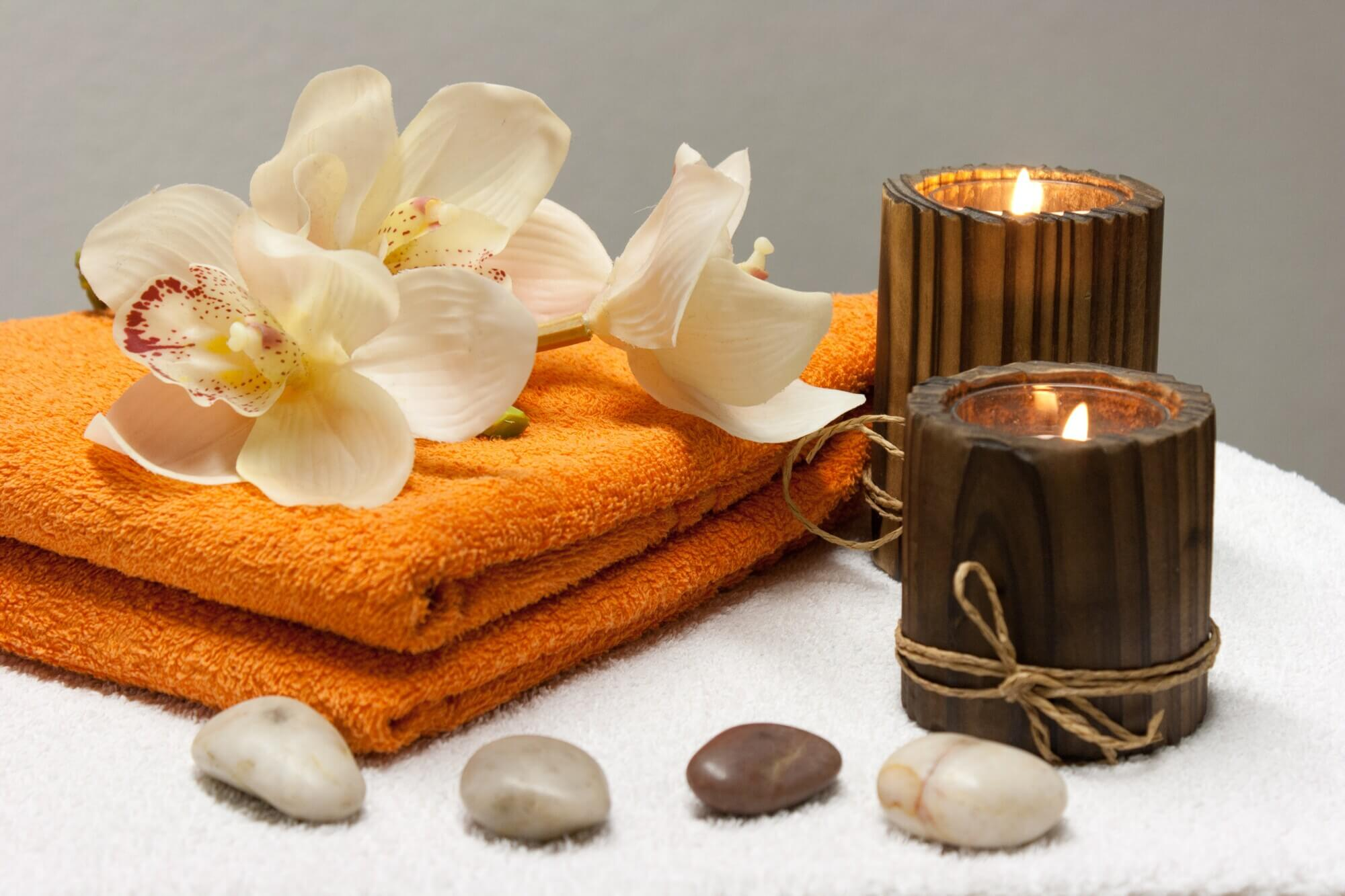 Flowers on orange towels with lit candles and some stones, a sauna or massage package