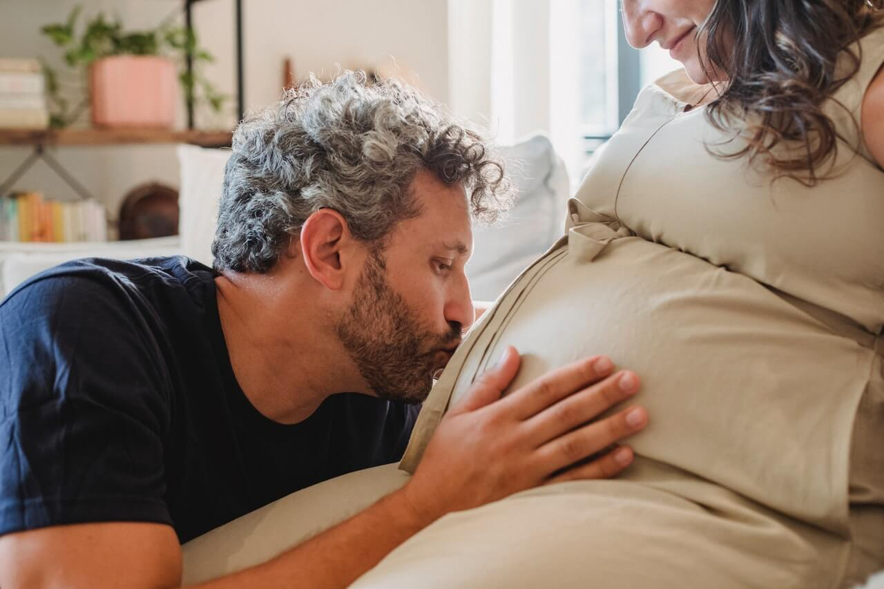 Man kissing his pregnant wife's belly and holding it with his hand