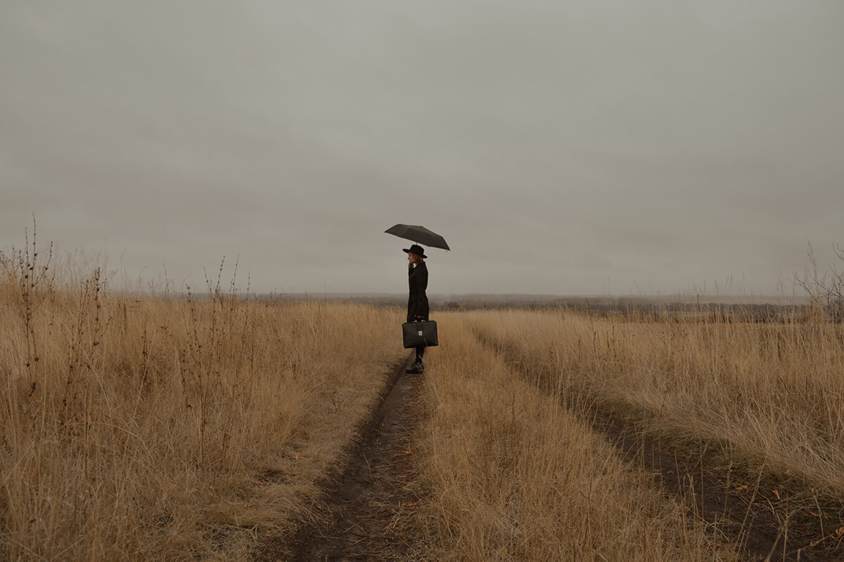 A depressed woman in black clothing and a briefcase standing in the rain in a field with her umbrella up