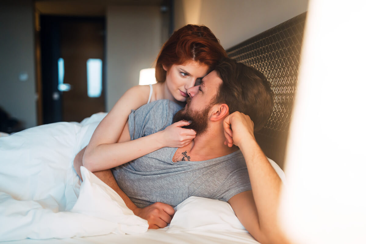 A couple in bed, the woman is seductively looking at the man