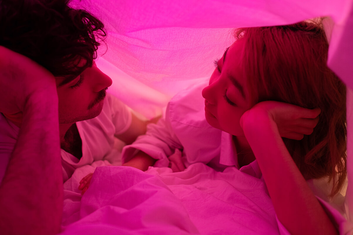 A man and woman under the bed sheets looking at each other, while pink light shines through the bed linen