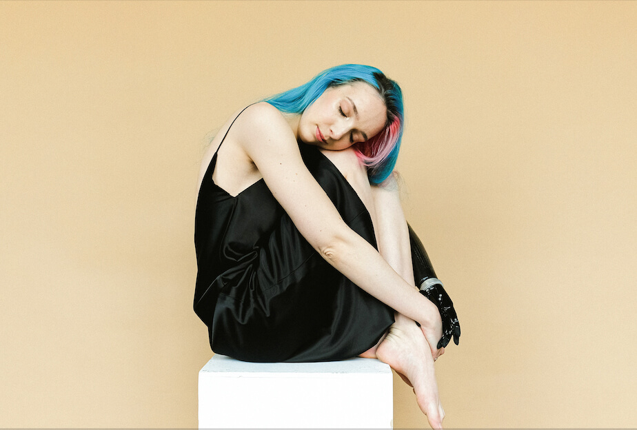 A woman with blue and pink hair, holding herself, accepting her body