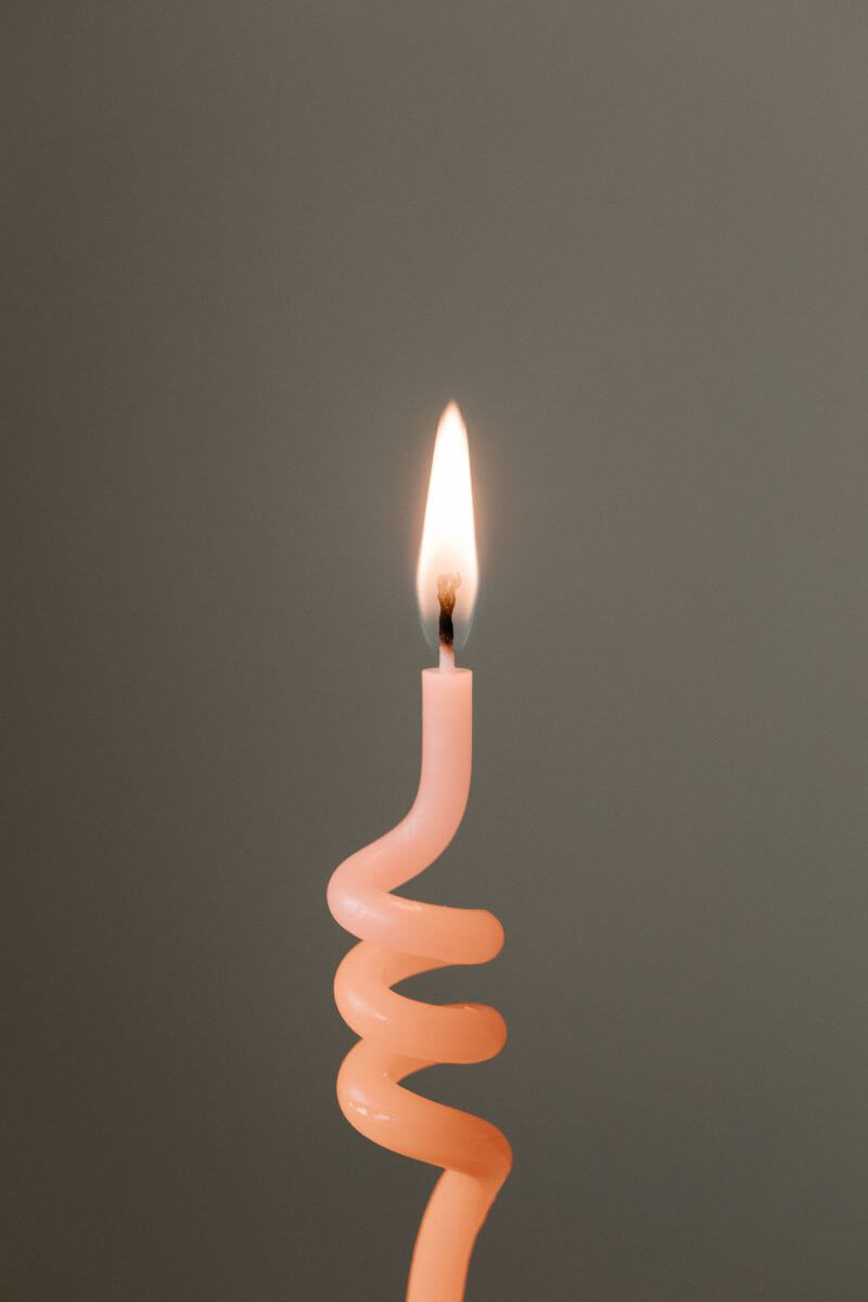 A lit candle formed like a coil.