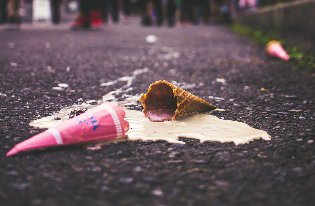 A close up of an ice cream cone that fell on the ground, all the ice melting away. That's a big setback if you were expecting a nice treat.