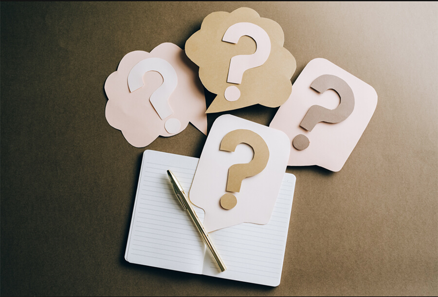 4 cut out pieces of paper with questions marks on them. Below, there's a notebook with a pen.