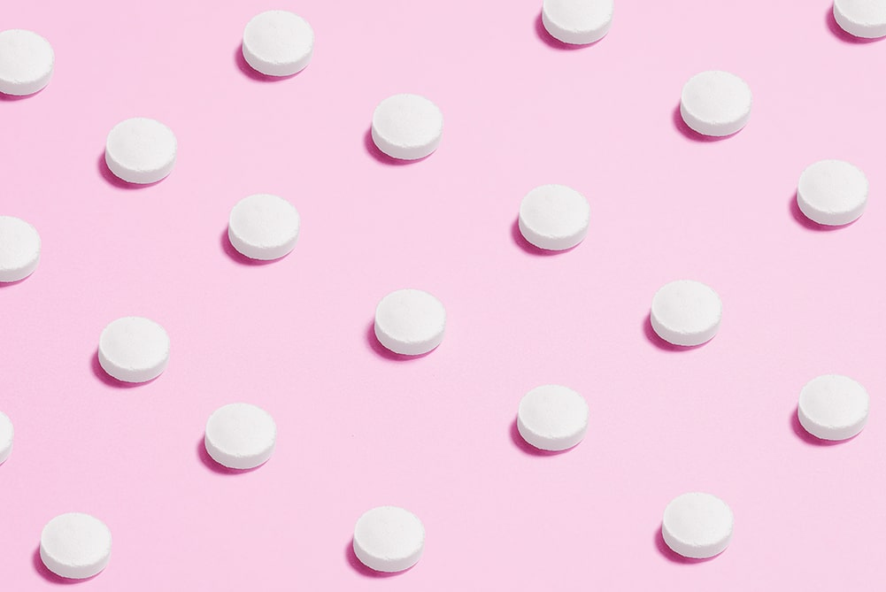 Birth control pills on a sheet of pink paper
