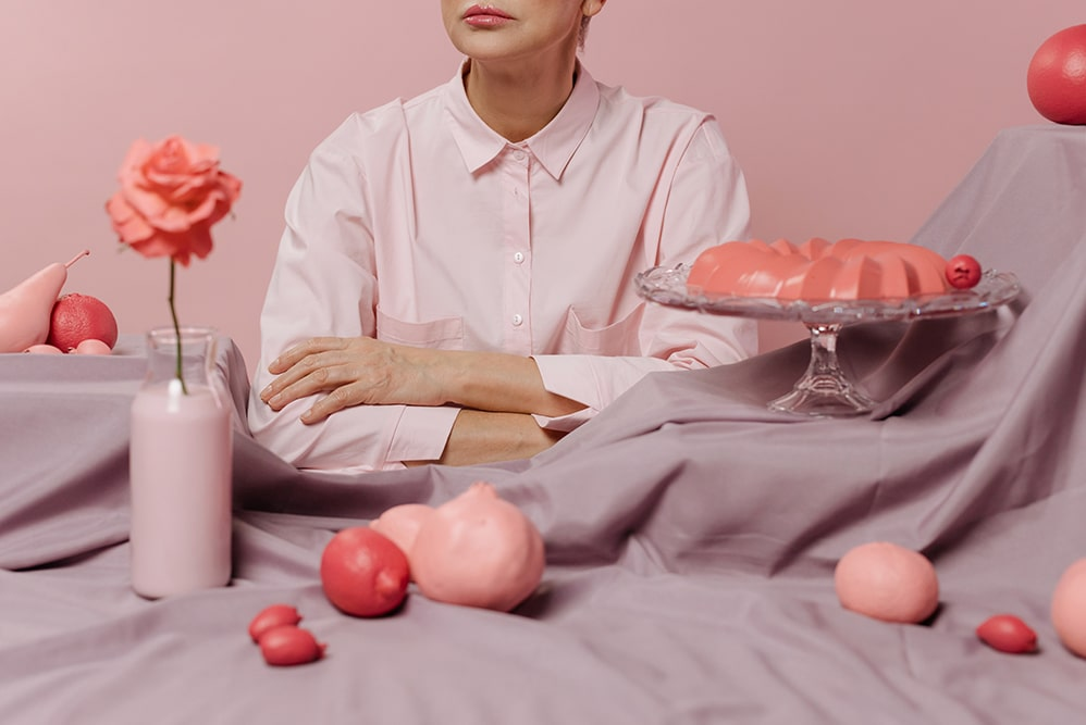 Lots of pink food in a pink setting with a woman wearing a pink shirt