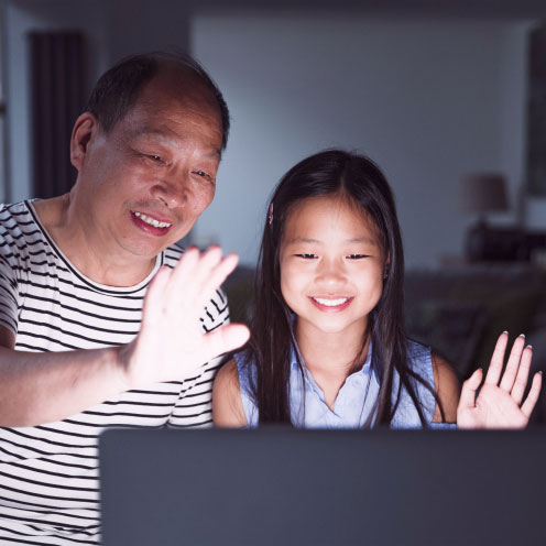 Little girl and her grandfather are using a laptop at home to video call their family. It is dark and the screen is illuminating their happy faces while they wave to the screen.