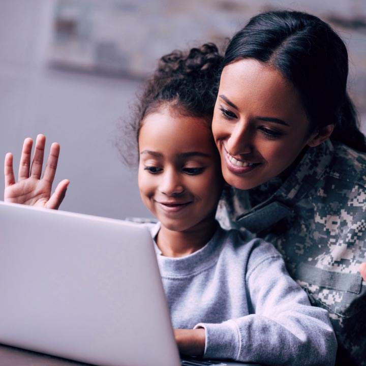 Happy mom with daughter using a laptop, watching TV shows while video chatting with other family members.