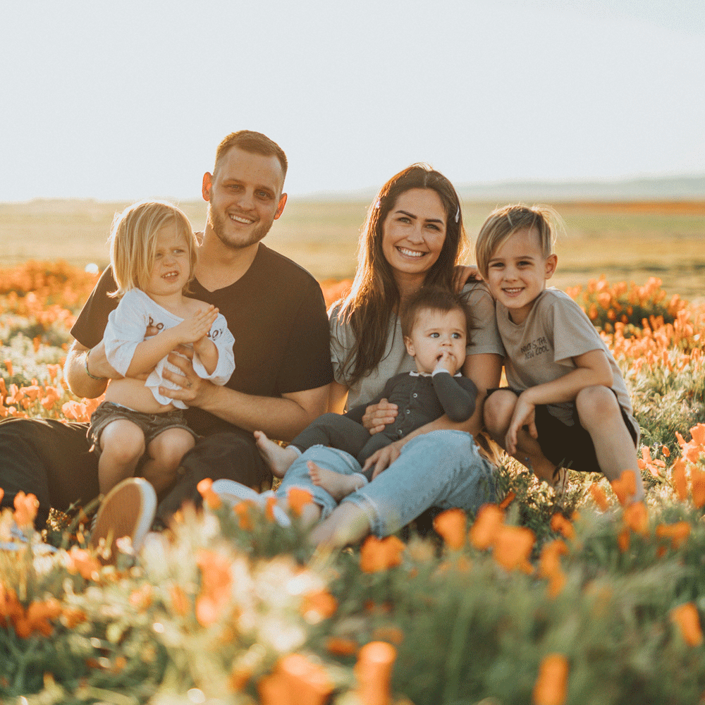 A family sitting in a field.