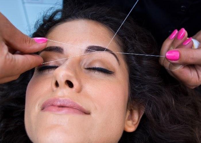 Female getting eye brows threaded