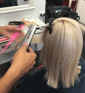 Keratin being heat infused into blonde hair.