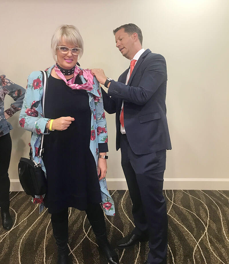 Vicki receiving a tie from JT Foxx, The world's top wealth coach.