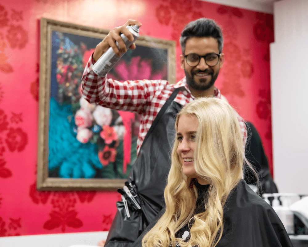 A hairdresser using hairspray on a client