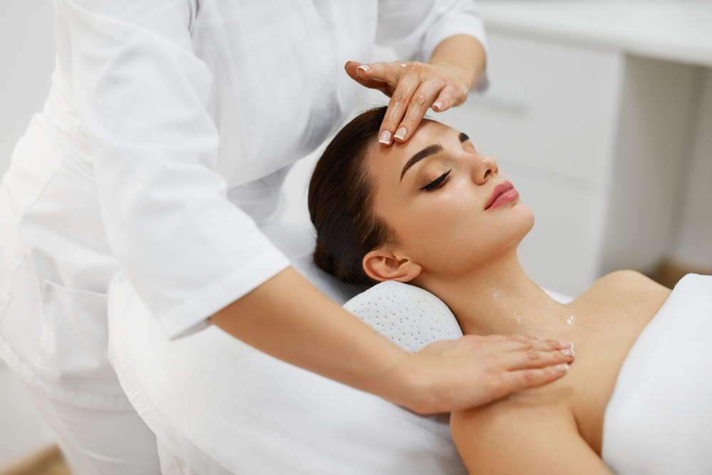 A brunette women lying down wrapped in a towel, receiving a head massage from a masseuse