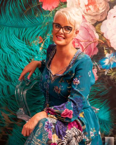 A master stylist in a blue floral dress, sitting with her legs crossed