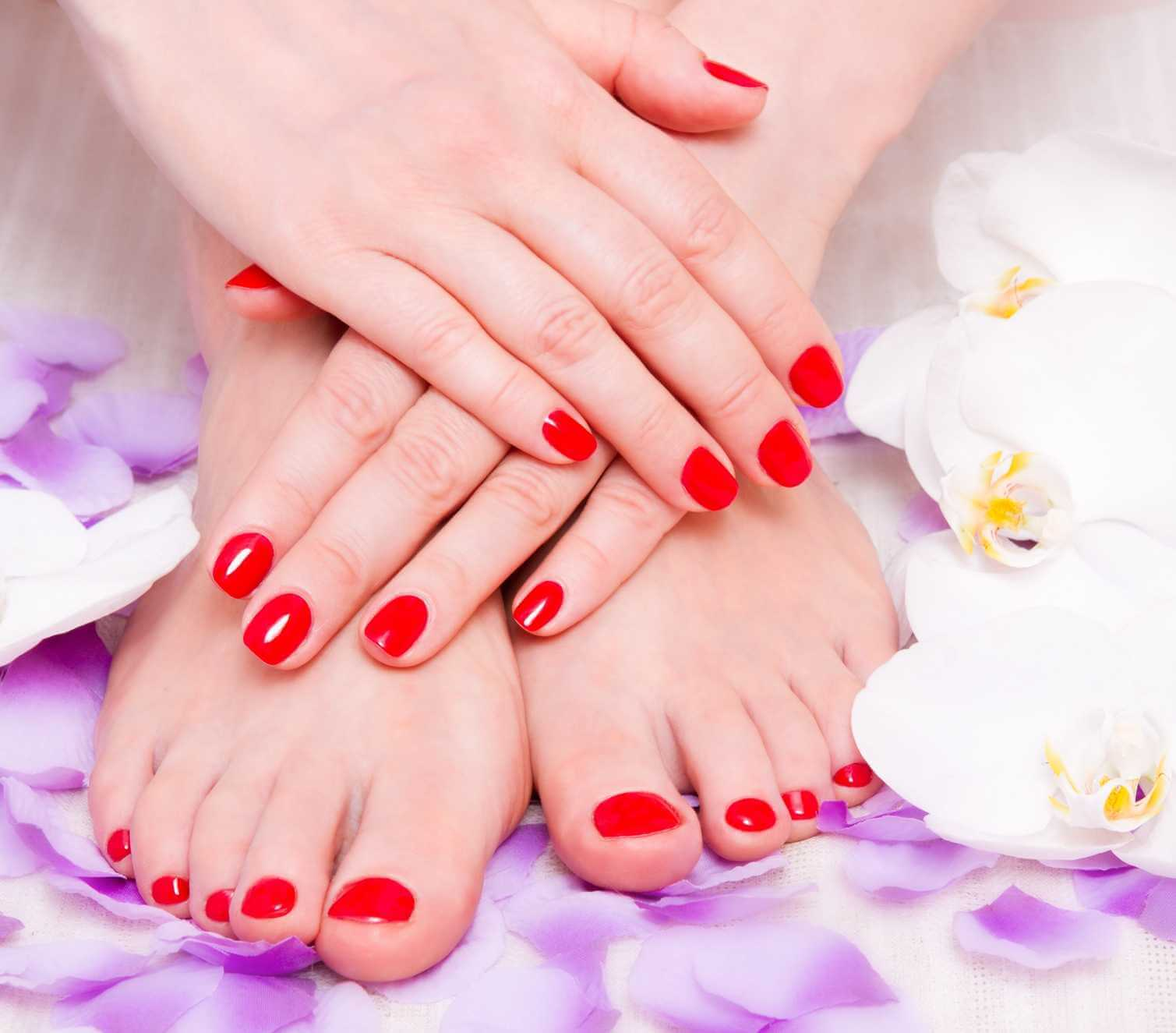 lady resting her hands with red fingernails on top of her feet with red toenails