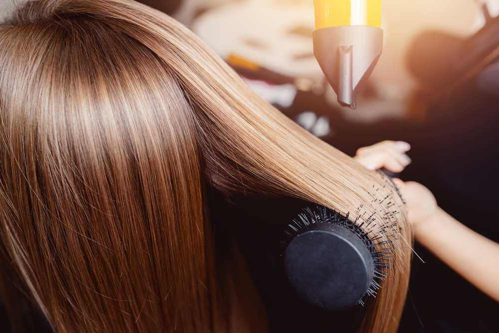 a lady getting her brown hair blow-dried