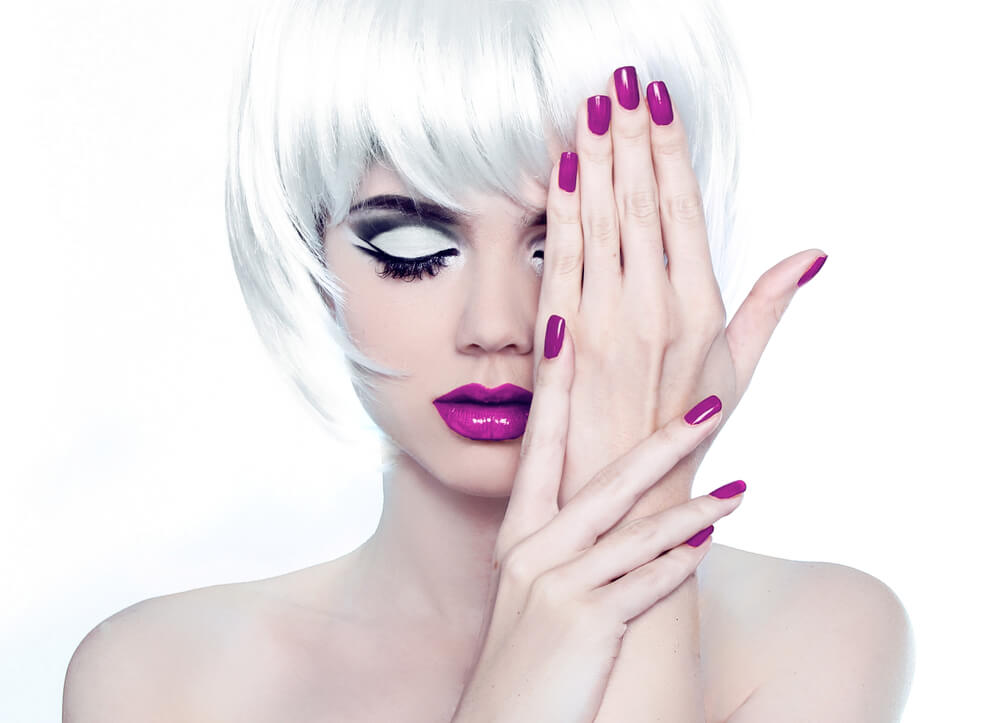 lady holding her pink manicure up against her pink makeup