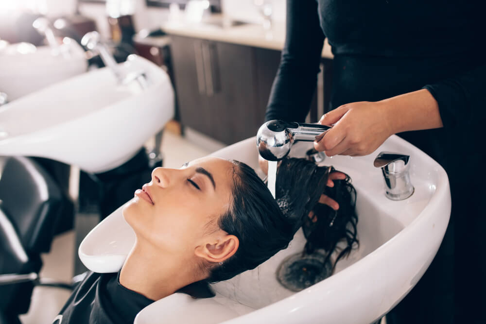 lady with black hair getting her hair washed in a salon
