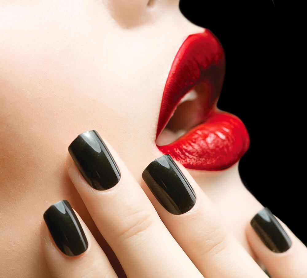 close up of lady's black fingernails nails resting against her face