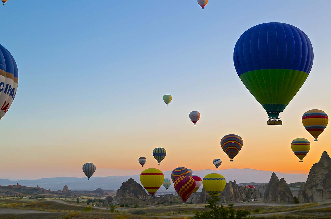 Several hot air balloons at sunset