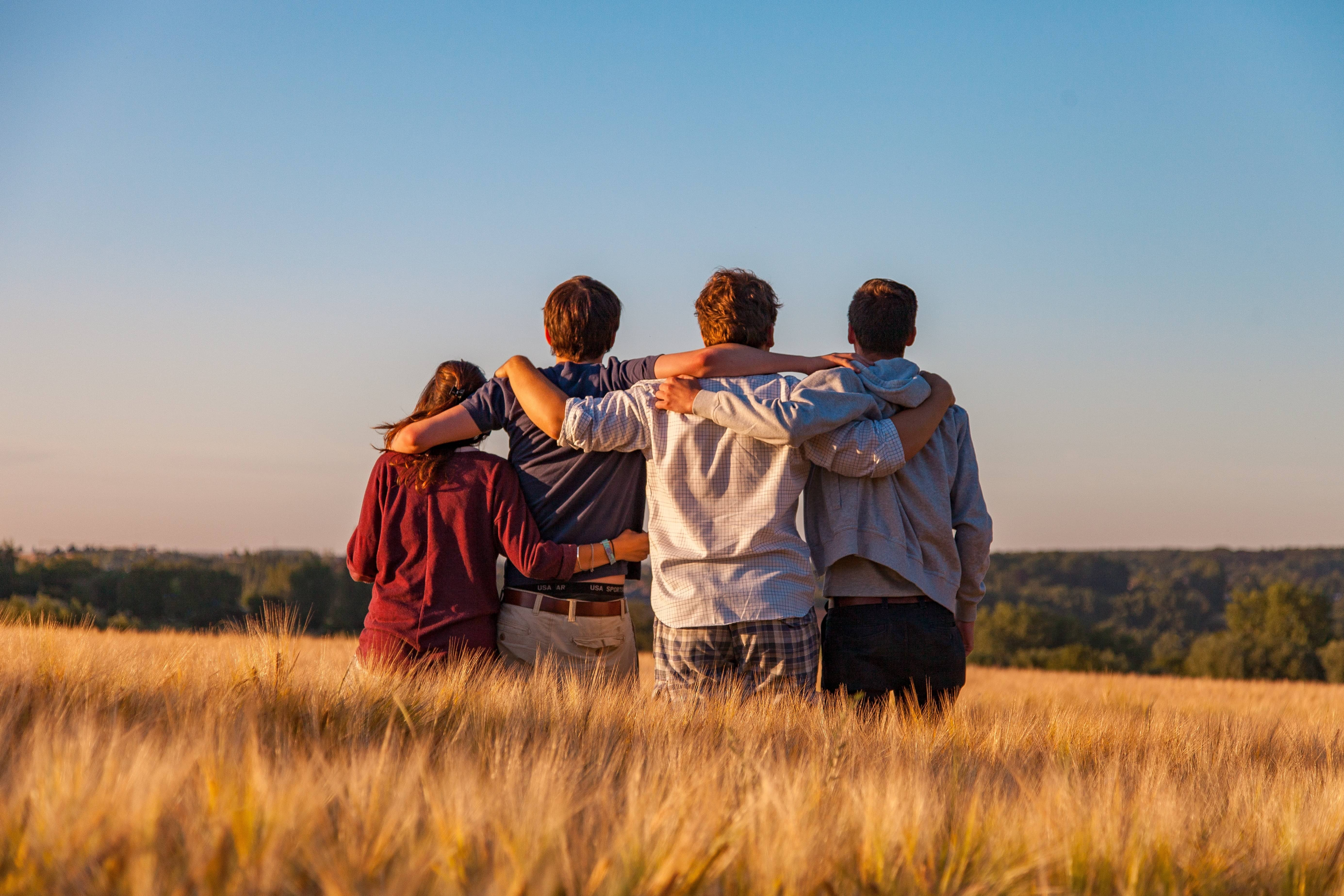 Four teens with their arms around each other
