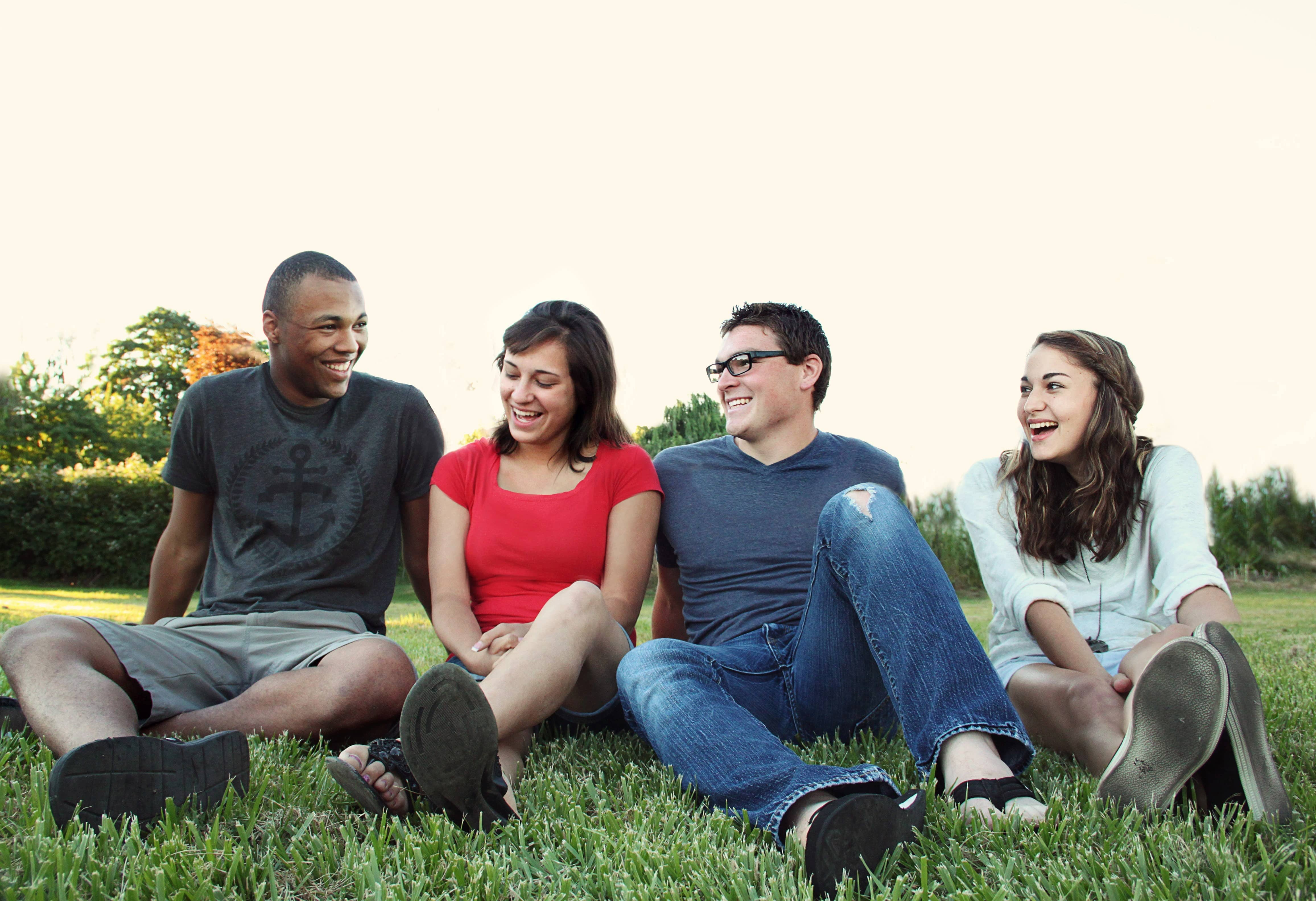 Four people sitting on the grass and laughing together