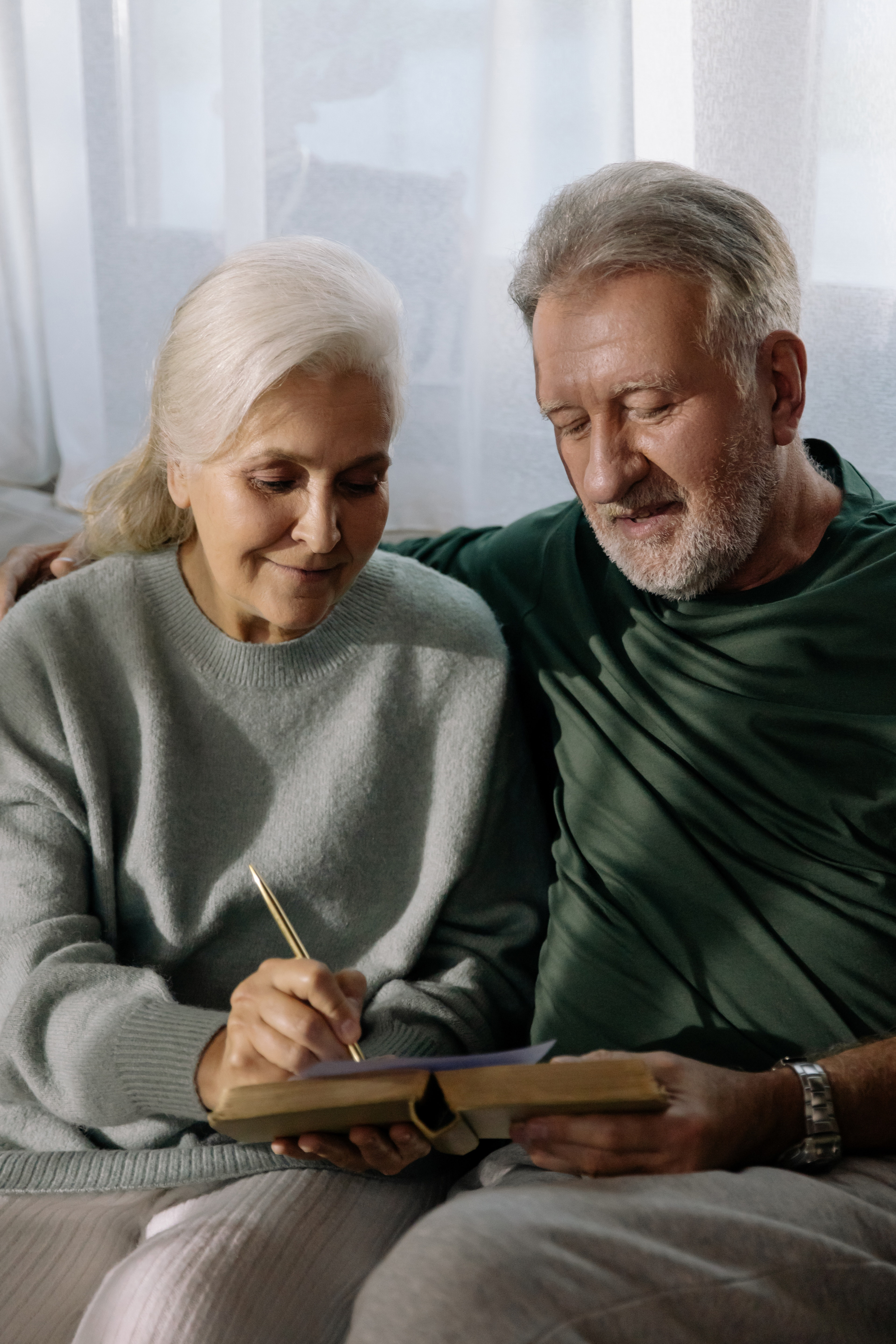 Two elderly people reading together