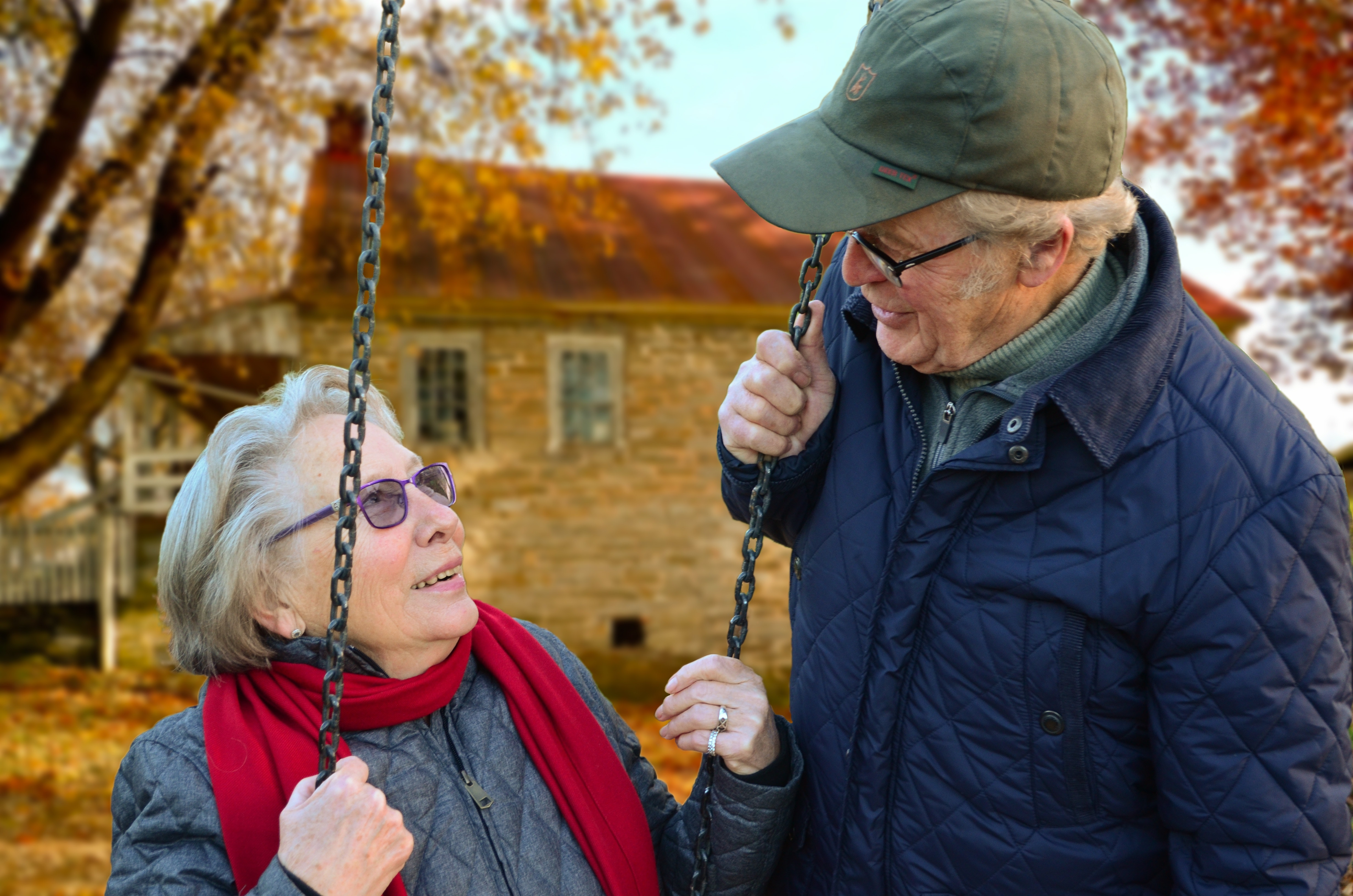 Two elderly people swinging together in the cold